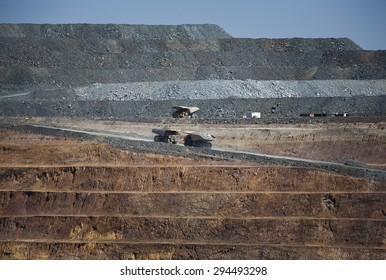 Yellow trucks drive out a dirt road in an open cast mine in New South Wales, Australia. Barrick Cowal Gold Mine.