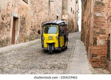 A yellow tuc tuc makes a tourist route through the old town of Caceres, Extremadura, Spain.