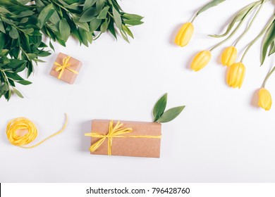 Yellow tulips and box with gift on white table top view