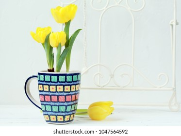 Yellow tulips with bulbs in a multicolored ceramic cup on a light background. Selective focus.