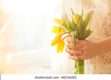 Yellow tulips. The girl in his arms. Tender girl. The girl in white. Morning. Tulips in hands. Gentle manicure. Fresh tulips.