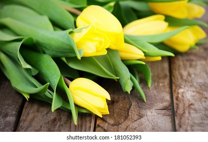 yellow tulips on rustic, wooden background