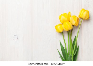Yellow tulips on wooden table. Top view with space for your text