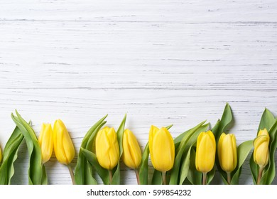 Yellow tulips on a wooden table, easter background, top view, flowers frame