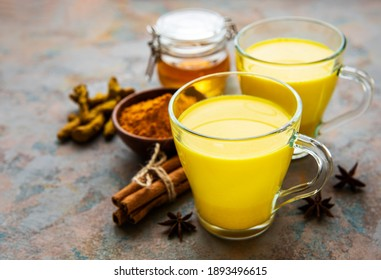 Yellow turmeric latte drink. Golden milk with cinnamon, turmeric, ginger  and honey over concrete background.
