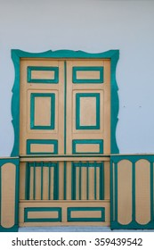Yellow turquoise green wooden door of a colonial house front