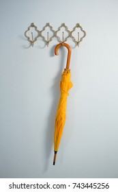 Yellow umbrella hanging on hook against white wall