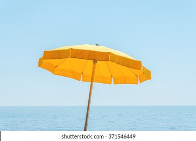 yellow umbrella near sea under blue sky
