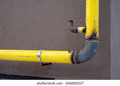 Yellow unfinished gas pipe on building wall. The concept of gasification of houses.