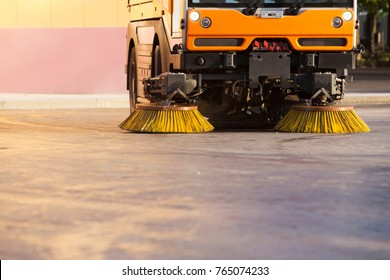 Yellow urban sweeper cleans road from dirt with a round brush