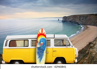 A yellow van with a surf board at the beach