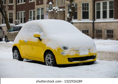 yellow vehicles covered with snow in the winter blizzard