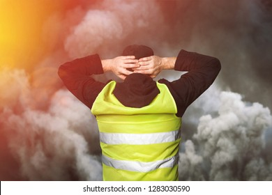 Yellow vests protests. Young man stands with his back and holds his hands on his head as a sign of obedience in tear gas. Concept of revolution and protest, struggle for equal rights