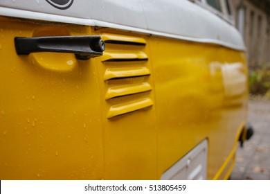 Yellow vintage car in perspective with black door handle