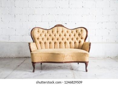 Yellow vintage sofa on white wall.