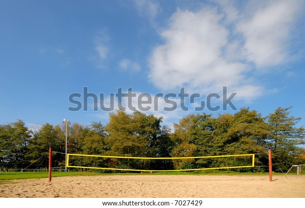 yellow volleyball net under blue clouded sky, in the background autumn trees