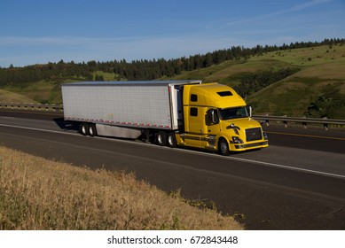 A Yellow Volvo Semi-Truck pulling a white trailer along a rural Oregon Highway. All markings removed.  June 20th, 2017 Rural Oregon, USA