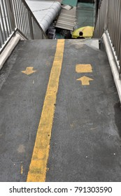 Yellow walking direction sign on the flying walkway on Rama IV road in Bangkok, Thailand