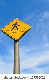 Yellow walking way sign with blue sky