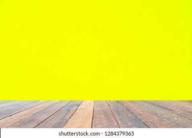 Yellow wall and empty wood desk .Blank space for text and images.