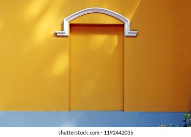 Yellow wall with fake window and white decoration