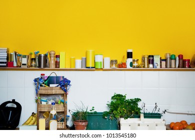Yellow wall in the kitchen with a  shelf with spices and herbs