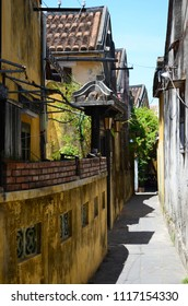 A yellow wall runs down a side street in Hoi An, with an arch over a gate. Yellow old buildings and trees line the street. The sky is blue. The street is deserted.