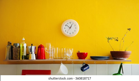 Yellow wall with utensils on a shelf and wall clocks