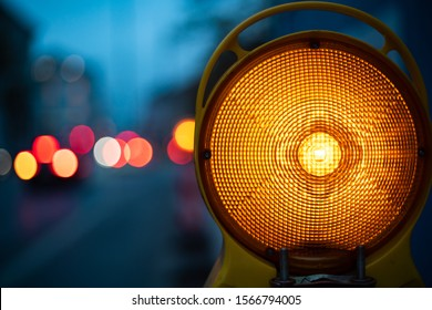 Yellow warning light on construction site. City bokeh of traffic lights in background of german city munich