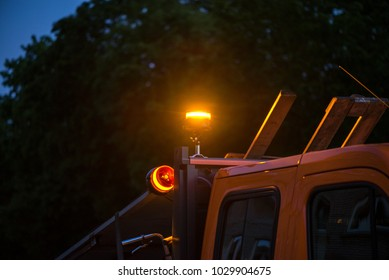 Yellow warning lights on dump truck. Road construction workers repairing highway road on late night. Loaders and trucks on newly made asphalt. Heavy machinery working on street.