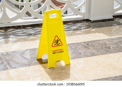 Yellow warning sign Caution Wet Floor on a marble floor in a public area. Preventing injuries to hotel guests during wet cleaning of halls and public places. - Shutterstock ID 1938566095