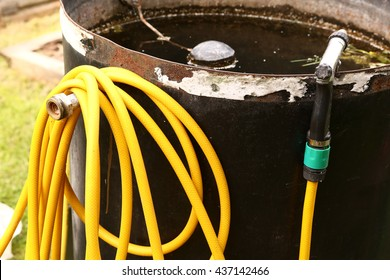 yellow water hose with nuzzle and barrel  close up photo on the green garden background
