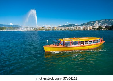 Yellow water taxi plies the clear waters of Lake Geneva with the Jet d'eau water fountain shooting a spray into the sky with a view of downtown buildings of Geneva, Switzerland. Horizontal copy space