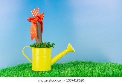 Yellow watering can with a stick with red bow in the garden