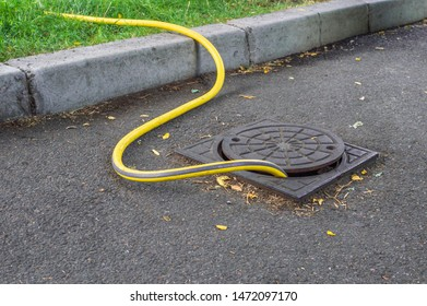 Yellow watering hose connected to the water hydrant in the manhole