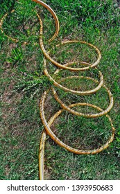 Yellow watering hose spiral in grass looking as snake