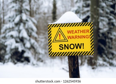 Yellow weather warning snow sign in the out of focus forest background