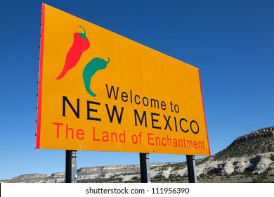 """A yellow """"welcome to New Mexico"""" sign in front of a blue sky"""