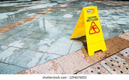 Yellow wet floor warning sign on the floor.