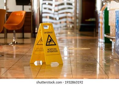 yellow wet floor warning sign and symbol on the passenger ferry restaurant floor