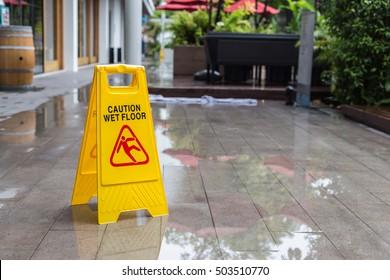 Yellow wet floor warning sign on the floor in hotel corridor