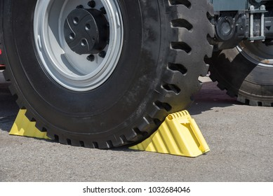 Yellow wheel chocks under the big black truck wheels