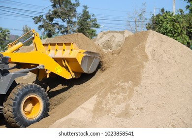 Yellow wheel  loader carry up sand from sand pile  in the filed with blue sky