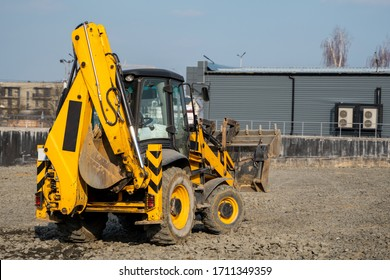 Yellow wheel loader Excavator machine working at construction site with a sand and gravel. Preparing of the fundament for a asphalting. Road construction site. Building of a parking.