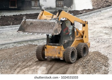 Yellow wheel skid-steer loader machine, loading and unloading gravel at construction. Worksite outdoors, heavy equipment machinery for heavy industry. Construction and renovation concept.