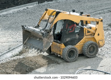 Yellow wheel skid-steer loader machine, loading and unloading gravel at construction. Worksite outdoor, heavy equipment machinery for heavy industry. Construction and renovation concept.
