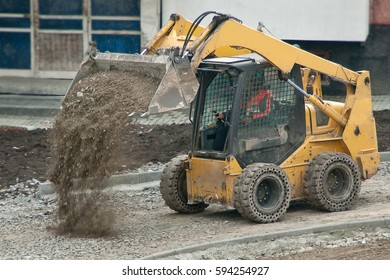 Yellow wheel skid-steer loader machine unloading gravel at construction area outdoors
