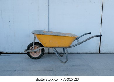 Yellow wheelbarrow parked on a side of the road.