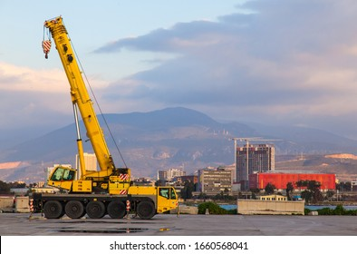 A yellow wheeled truck crane stands in the port of Izmir Turkey. Heavy wheeled loading equipment.