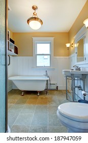 Yellow and white bathroom with window, washbasin stand and claw foot tub.